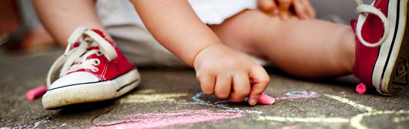 boy drawing on pavement with chalk