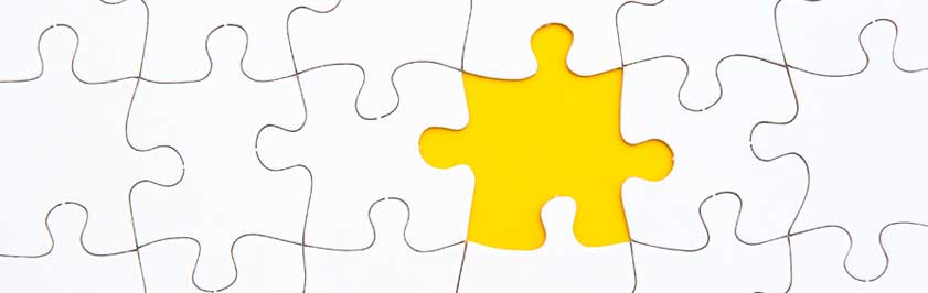 Yellow jigsaw puzzle piece surrounded by white jigsaw puzzle pieces